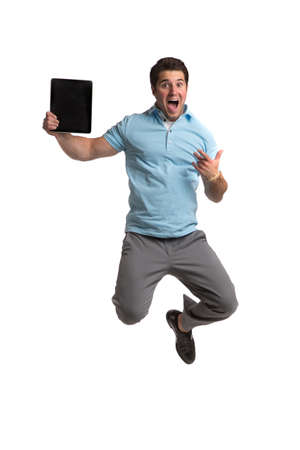 excited man: Young Businessman Holding Tablet PC Jumping cheerfully on Isolated White Background