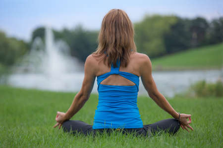 Mid Age Yoga Woman Pose Outdoor Practice in front of Park Water Fountain photo