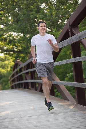 Jogging Healthy Looking Young Man Cross Bridge Under Morning Sunlight photo