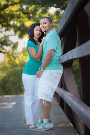 Young Hispanic Couple Engagement Picture Outdoor Portrait Back Lit by Bridge photo