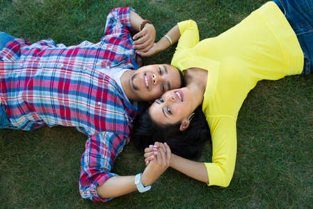 Young Hispanic Couple Lying on Grass Engagement Picture Outdoor Portrait photo
