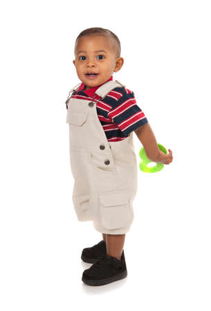 boy body: Smiling 1-year old baby boy standing Full Body Length Portrait holding toy on isolated background