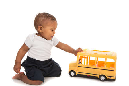 children at play: Little African American Baby Boy Pushing Toy School Bus on White Background