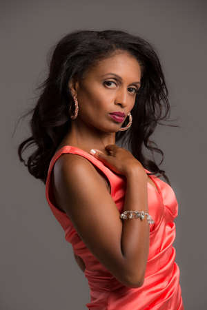 African American Female Model Portrait Low Key on Grey Background Wearing Red Dress photo