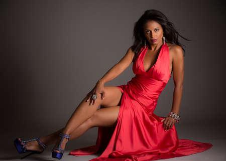 modellini: African modello americano femminile Ritratto Low Key su sfondo grigio che indossa un abito rosso