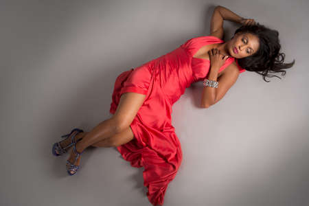 African American: �frica Modelo Centroamericano de Mujeres Retrato Low Key en fondo gris con un vestido rojo Foto de archivo
