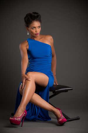 flying hair: African American Female Model Portrait Low Key on Grey Background Wearing Blue Dress