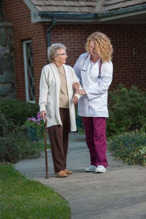 enfermeria: Nurse Helping Walking senior con ca�a al aire libre en la madrugada frente a la casa Foto de archivo