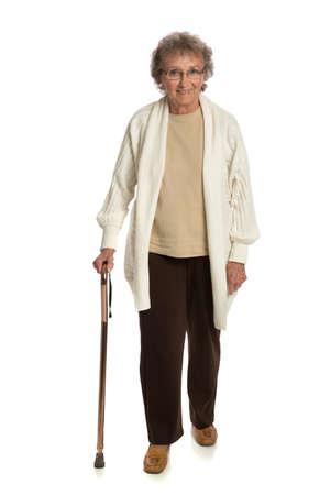 senioren wandelen: 80 Jaar Oude Vrouw Lopen met Cane Geà ¯ soleerd op witte achtergrond