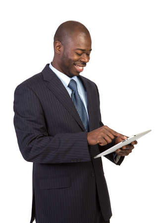 touch pad: Laughing Young African American Male Businessman Texting on a Touch Pad Tablet PC on Isolated White Background Stock Photo