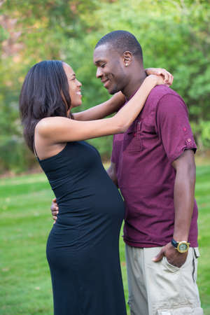 Black Couple Expecting Pregnancy Woman Hugging and Kissing Outdoor photo