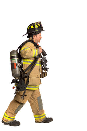 Firefighter holding mask and airpack fully protective suit walking on isolated white background photo