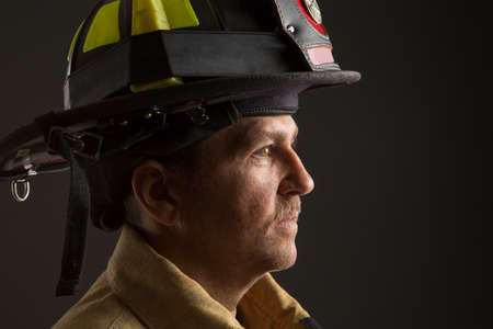 sholders: Serious looking confident firefighter Headshot Profile View Portrait on Dark Background