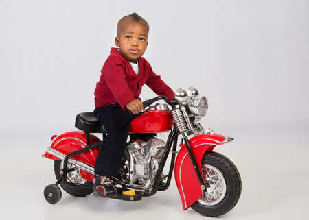 One Year Old Boy Riding Motorbike on Grey Background