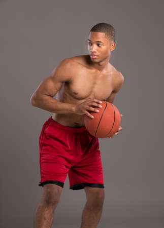 Young Black College Student Holding Basket Ball on Grey Background photo