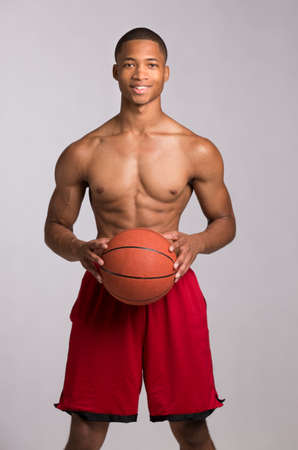 boy in shorts: Young Black College Student Holding Basket Ball on Grey Background