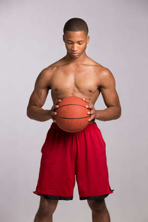 Young Black College Student Holding Basket Ball on Grey Background Stock Photo - 16120450