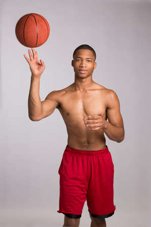 Young Black College Student Holding Basket Ball on Grey Background Stock Photo - 16120440