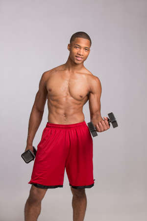Young African American Athlete Holding Lifting Dumbbells on Grey Background photo