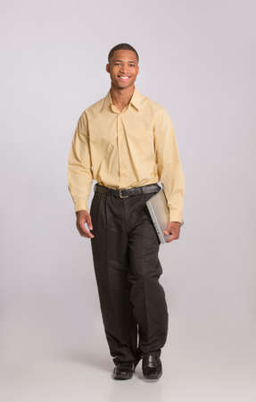 Young African American Male Holding Laptop Walking Full Body Length on Grey Background photo