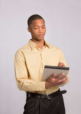 Young African American Male Writing on Notepad on Grey Background photo