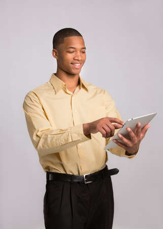 Young African American Businessman Texting on Tablet PC Pad on Grey Background photo