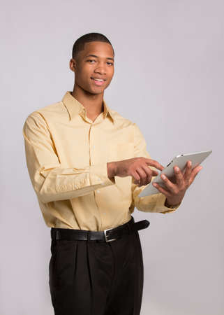 Young African American Businessman Texting on Tablet PC Pad on Grey Background Stock Photo - 16120438