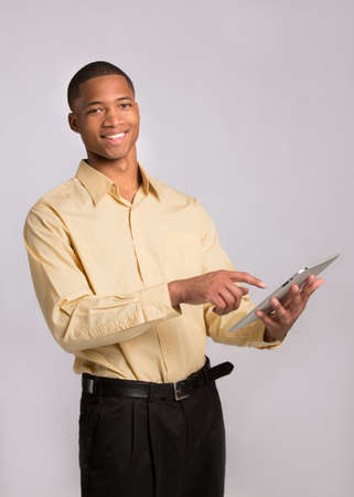 Young African American Businessman Texting on Tablet PC Pad on Grey Background Stock Photo - 16120433
