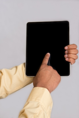 Close up of Hand Pointing to Tablet PC on Grey Background Stock Photo