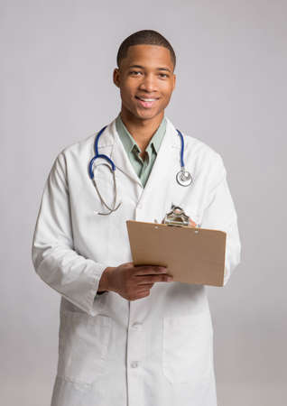 modern doctor: African American Doctor Holding Notepad Smiling on Grey White Background Stock Photo