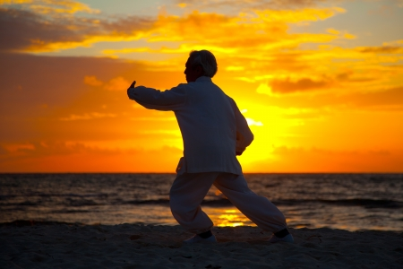Chinese Elderly Woman Performing Taichi Outdoor by the beach under sunset sunrise silhouette Imagens