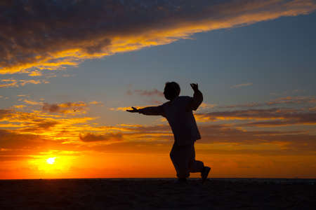 Chinese Elderly Woman Performing Taichi Outdoor by the beach under sunset sunrise silhouette Stock Photo