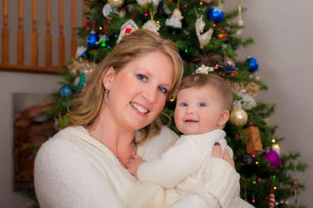 Mom Holding Cute Infant Baby in front of Christmas Tree Wearing Sweater Stock Photo - 21499237