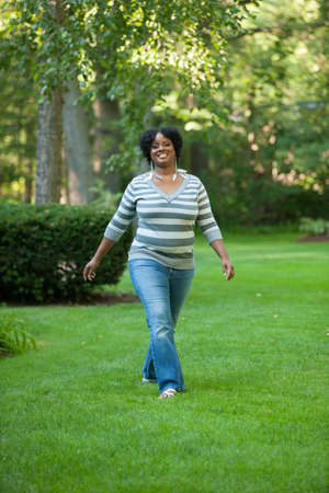 backyard woman: Smiling Pretty Young African American Female Walking Outdoor in Park