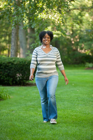 Smiling Pretty Young African American Female Walking Outdoor in Park photo