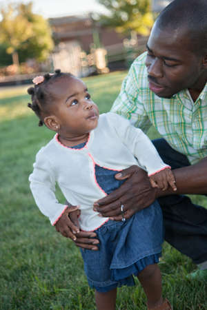 Little Smiling African American Girl Playing with Dad Outdoor photo