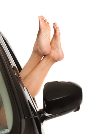Female feet stick out of car window isolated on white background Stock Photo