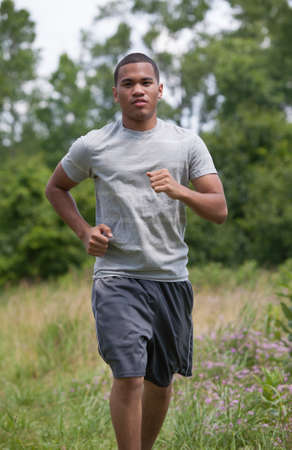Healthy Looking Young African American Man Jogging in the Woods photo