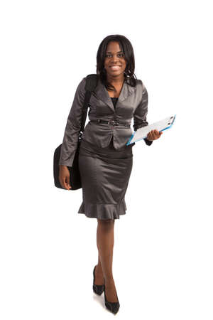 business dress: Young African American Businesswoman Holding Folders on Isolated White Background Walking