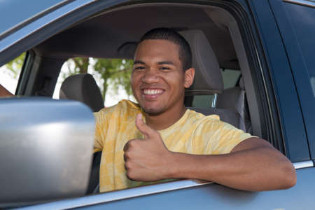 in behind: Young Smiling African American Male Thumb up in a Car Stock Photo