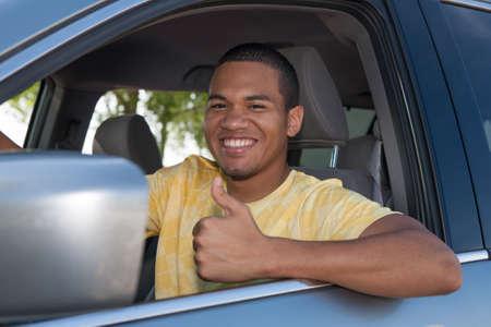 man driving: Young Smiling negra masculina Thumb hasta en un coche