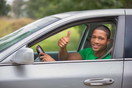 personen: Jonge Smiling African American man duim omhoog in een auto Stockfoto