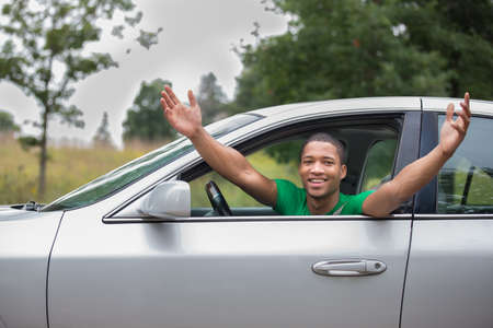 Joyful African American Male Driver Arms Out of Car Window photo