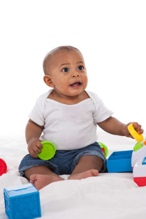 early education: 7-month old african american baby  boy playing with toys on white background