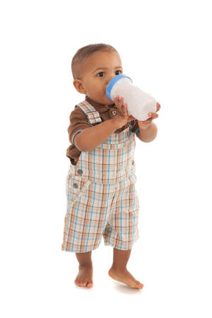 standing water: one year old baby boy holding milk bottle standing on isolated white background Stock Photo