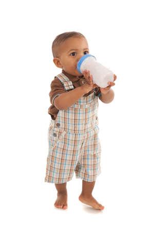 teteros: un a�o de edad beb� que sostiene la botella de leche de pie en el fondo blanco aislado