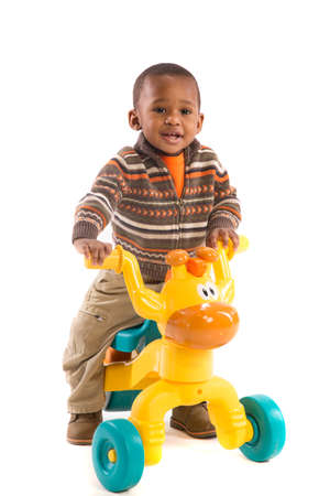 One Year Old Boy Riding toy tricycles isolated on White Background photo