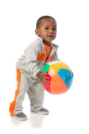 1 year old: 1 year old African American baby boy standing holding beach ball on isolated background Stock Photo