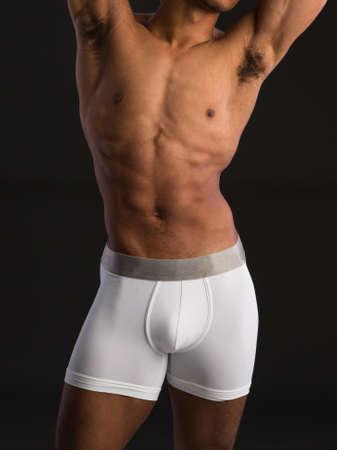 naked male body: Black Male Wearing White Underwear on Dark Background