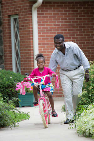 grand daughter: Smiling African American Man Helping Little Girl Biking Outdoor, grandpa and grand daughter Stock Photo